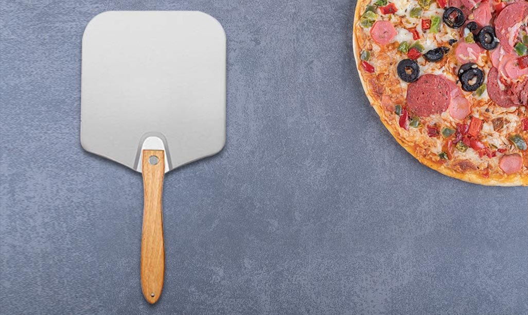 12-Inch Foldable Wood Handle Pizza Peel on surface with pizza